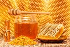 在瓶子的蜂蜜有浸染工、蜂窝、花粉和ci的 免版税库存照片
