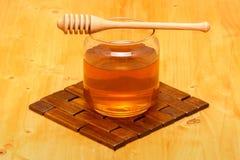 在瓶子的蜂蜜有浸染工的 免版税库存图片