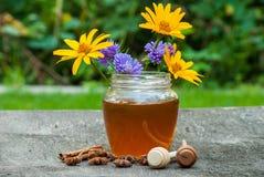 在瓶子的蜂蜜有蜂蜜匙子的 库存照片