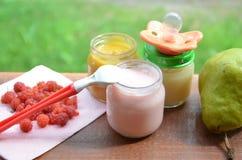 在瓶子纯汁浓汤的婴儿食品捣碎了在叶子背景的食物,用梨香蕉、安慰者和匙子 图库摄影