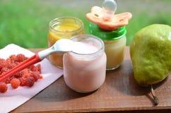 在瓶子纯汁浓汤的婴儿食品捣碎了在叶子背景的食物,用梨香蕉、安慰者和匙子 免版税库存照片