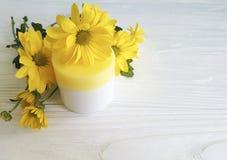 在瓶子黄色菊花产品花白色木的化妆润肤霜奶油香脂健康 免版税库存照片