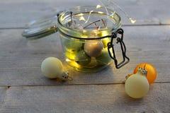 在瓶子玻璃的蜡樱桃与LED光和圣诞节球 免版税图库摄影