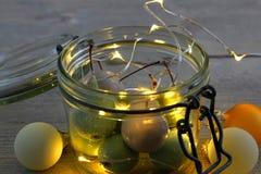 在瓶子玻璃的蜡樱桃与LED光和圣诞节球 免版税库存照片