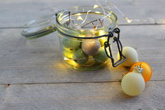 在瓶子玻璃的蜡樱桃与LED光和圣诞节球 免版税库存图片