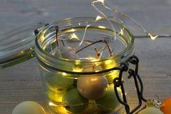 在瓶子玻璃的蜡樱桃与LED光和圣诞节球 库存照片