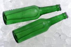 在瓶的冰镇啤酒在冰 免版税库存照片