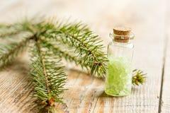 在瓶的化妆云杉的盐有毛皮的在木桌背景分支 免版税库存照片