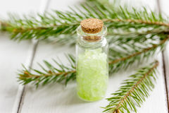 在瓶的化妆云杉的盐有毛皮的在白色木桌背景分支 免版税图库摄影