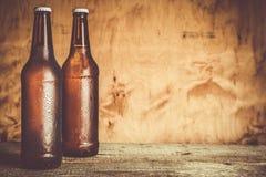 在瓶的啤酒有冰下落的 免版税库存照片