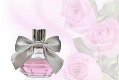 在瓶的女性香水有在花卉背景的弓的 免版税图库摄影