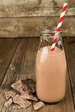 在瓶的巧克力牛奶在木头 库存图片