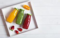 在瓶的新鲜的桔子、草莓和硬花甘蓝圆滑的人用果子和薄菏在一个白色木土气箱子和在一白色backgro 图库摄影