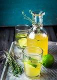 在瓶的柠檬水和在葡萄酒的两块玻璃金属化盘子 木背景 免版税库存图片