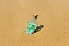 100在瓶的欧元钞票在海滩的岸发现了 库存图片
