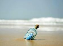 20在瓶的欧元钞票在海滩的岸发现了 免版税库存照片