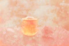 在瓶的蜂蜜与在桃红色花abstct背景上升了 库存图片