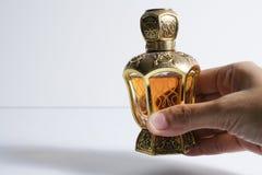 在瓶的阿拉伯香水在白色backgro用手举行了,隔绝 免版税图库摄影