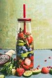 在瓶的鲜美被灌输的水有饮料秸杆和成份的,正面图 水调味用五颜六色的果子、莓果和草本 免版税库存照片