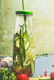 在瓶的鲜美被灌输的水有饮料秸杆和成份的,正面图 水调味用绿色果子、黄瓜和草本 库存图片