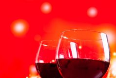 在瓶附近的两块红葡萄酒玻璃反对红灯背景 免版税库存照片