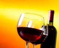 在瓶附近的两块红葡萄酒玻璃反对金黄光背景 免版税库存照片