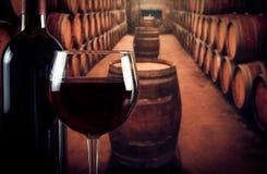 在瓶附近的酒杯在有空间的老葡萄酒库里文本的 免版税库存照片