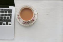 在瓷杯子的银色膝上型计算机和牛奶茶 免版税库存照片