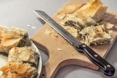 在瓷盛肉盘切在木切板和供食的传统乳酪菠菜卷饼 免版税库存图片