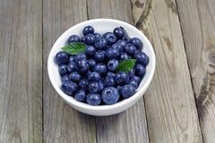 在瓷碗的蓝莓在木桌上 免版税库存照片