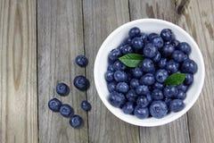 在瓷碗的蓝莓在木背景 库存图片