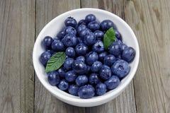 在瓷碗的蓝莓在木背景 库存照片
