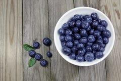 在瓷碗的蓝莓在木背景 免版税图库摄影