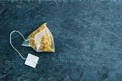 在甘菊茶袋子的特写镜头在石基体 免版税库存照片