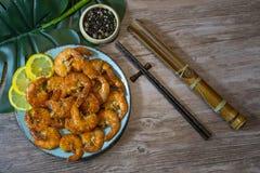 在甜和辣调味汁亚洲盘顶视图的虾与在一张木桌上的筷子 库存照片