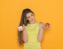 在甜点和健康食物之间的困难的选择 免版税库存图片