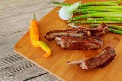 在甜调味汁下的新鲜的给上釉的被烘烤的大牛肉肉肋骨大块与蕃茄辣椒桃红色 图库摄影