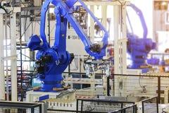 在生产线制造商工厂的工业采摘机器人 免版税库存图片