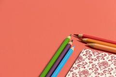 在生动的珊瑚的桌面与在角落和颜色铅笔的笔记本 免版税库存图片