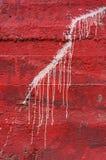 在生动的红色混凝土墙3上的白色水滴油漆 库存图片