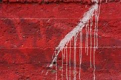 在生动的红色混凝土墙1上的白色水滴油漆 免版税库存图片