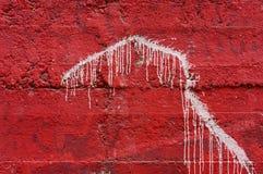 在生动的红色混凝土墙2上的白色水滴油漆 库存图片