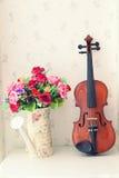 在生存rooem的小提琴和花花束 免版税图库摄影