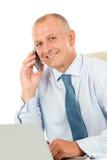 在生意人服务台办公室坐的微笑之后 免版税库存图片
