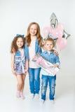 在生日聚会的俏丽的孩子和在牛仔裤衣裳的礼物呆在一起 陈腐 微笑 图库摄影