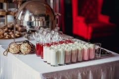 在生日聚会的棒棒糖用很多另外糖果、杯形蛋糕、蛋白牛奶酥和蛋糕、奶昔和汁液在玻璃杯子 deco 免版税库存照片