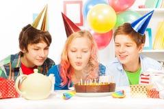 在生日聚会的美丽的青少年的女孩打击蛋糕 免版税库存照片