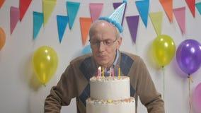 在生日蛋糕的资深吹的蜡烛 股票录像