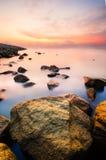在生苔岩石的日出在海洋附近用乳状看的水 免版税库存图片