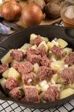 在生铁平底锅的未加工的咸牛肉马铃薯泥 免版税库存图片